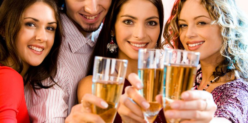 Portrait of four people holding glasses of  champagne,